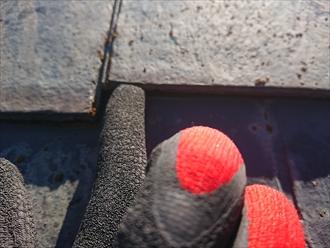 雨水を吸い込みスレート屋根材が反っている様子。回りには塗装するときに使われるはずのタスペーサーが見当たりません。