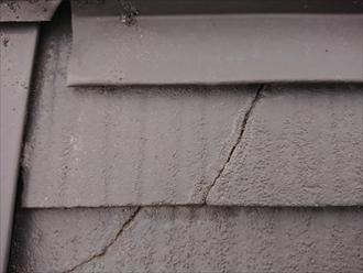 棟板金近くの化粧スレートにクラックが入っており、雨水を吸い込んだためか白くクラック周辺が変色しております。