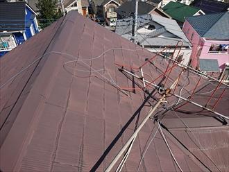 強風によりテレビ用アンテナが屋根の上で倒れてしまっている様子