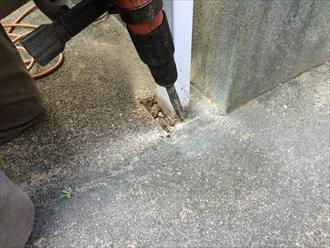 雨樋交換のためにコンクリートの地面を削る