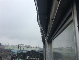 工場雨樋から雨水がは溢れている