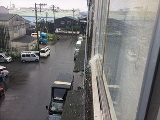 工場雨樋から溢れた雨水が窓に当たっている
