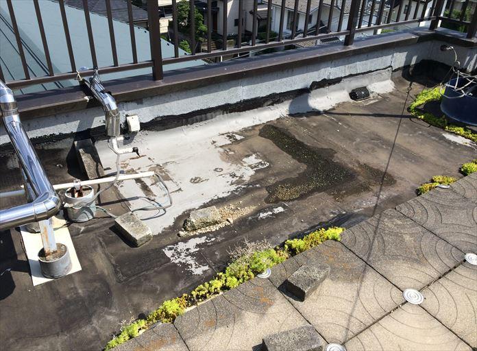 敷石の置かれた屋上の陸屋根を調査
