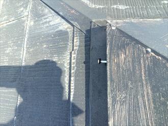 棟板金の側面から太い釘が抜け出いる