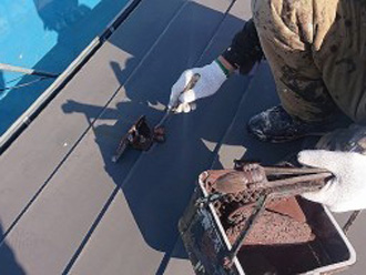 トタン屋根の塗装の様子 刷毛を使って雪止め金具を塗装