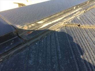 棟板金とスレートの隙間がコーキングで埋まっている